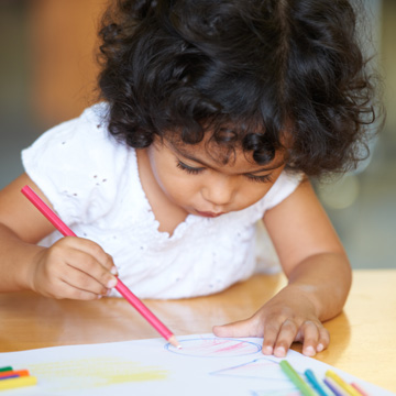 little girl writing on paper with a colored pencil