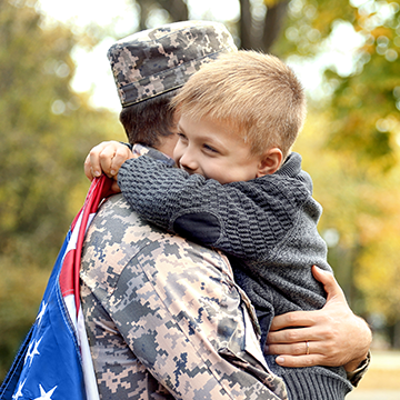 niño abrazando a su padre con uniforme