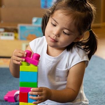 niña pequeña apilando legos