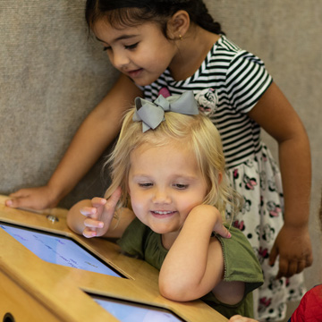 two girls playing on ipad at table